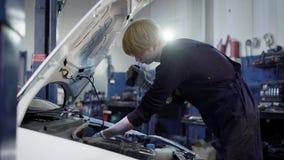Seitenansicht des Technikers Wartung vom Auto in der Garage machend lizenzfreies stockfoto