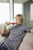 Seitenansicht des trinkenden Weins des Mittelerwachsenmannes im Wohnzimmer zu Hause Stockfotos