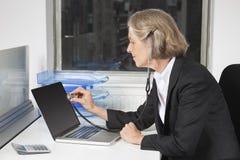 Seitenansicht des Untersuchungslaptops der älteren Geschäftsfrau mit dem Gebrauch des Stethoskops am Schreibtisch Stockfotografie
