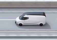 Seitenansicht des weißen selbst-treibenden Lieferwagens, der auf Landstraße fährt Lizenzfreie Stockfotografie