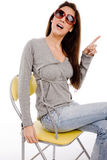 Seitenansicht des Zeigens der Frau sitzend auf Stuhl Lizenzfreies Stockfoto