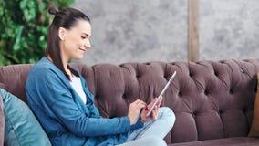 Seitenansicht, die jugendliches junges Mädchen unter Verwendung des Tabletten-PC sitzt auf Couch am Cosinesswohnzimmer lacht stock footage