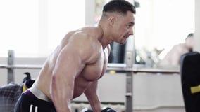 Seitenansicht - ein starkes Bloß-chested Mann-Training mit Dummköpfen stock video footage