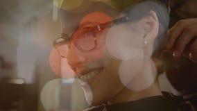 Seitenansicht einer Frau, die beim Haben eine Haar getan mit bokeh Effekt auf den Vordergrund lächelt stock video