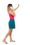 Seitenansicht einer Frau, die mit einem Handy geht Stockbilder
