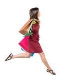 Seitenansicht einer Frau, die mit Einkaufstaschen springt Lizenzfreies Stockfoto