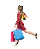 Seitenansicht einer Frau, die mit Einkaufstaschen springt Lizenzfreie Stockfotos