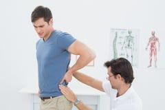 Seitenansicht einer männlichen Physiotherapeutenuntersuchung bemannt zurück Lizenzfreies Stockbild