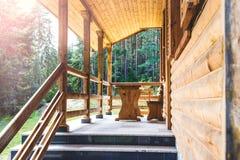 Seitenansicht einer offenen Veranda vor einem hölzernen Waldhäuschen Kiefernwald unter der Sonne strahlt im Hintergrund aus Stockbilder