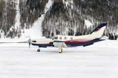 Seitenansicht einer Propellerart Privatflugzeug, das im schneebedeckten Flughafen von St. Moritz Switzerland im Winter startet stockbilder
