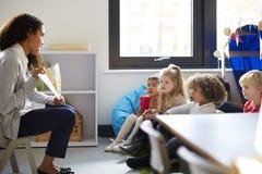 Seitenansicht einer weiblichen Kindergärtnerin, die auf einem Stuhl zeigt den Kindern ein Buch in einem Klassenzimmer sitzt stockbild