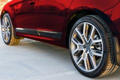Seitenansicht eines Autos Reifen und Leichtmetallrad eines modernen roten Autos aus den Grund bei dem Sonnenuntergang Autoäußerde Lizenzfreie Stockbilder