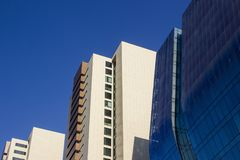 Seitenansicht eines Blaus kurvte modernes Unternehmenshohes gebäude und zwei gelbliche Bürogebäude Lizenzfreies Stockfoto