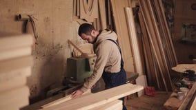 Seitenansicht eines craftman, das an einer elektrischen Säge mit Holz arbeitet Drückt den Holzklotz durch Hände stock video
