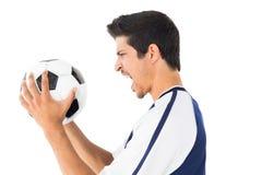 Seitenansicht eines Fußballspielerschreiens Lizenzfreie Stockbilder