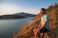 Seitenansicht eines glücklichen Mannes mit dem Rucksack, der Meer beim Sitzen auf Hügel gegen Himmel während des sonnigen Tage lizenzfreie stockfotografie