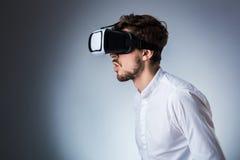 Seitenansicht eines jungen Kerls, der einen VR-Kopfhörer verwendet stockbild