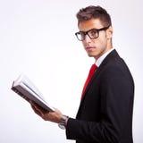 Seitenansicht eines jungen Kursteilnehmers, der ein Buch anhält Lizenzfreie Stockfotografie