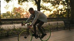 Seitenansicht eines jungen lächelnden Mannes in der Sonnenbrille, die morgens einen Park oder einen Boulevard des Fahrrades radfä stock footage
