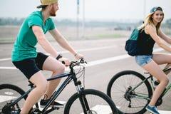 Seitenansicht eines jungen Paares auf Zyklus reiten in Landschaft Stockfoto