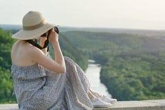 Seitenansicht eines Mädchens mit einer Kamera Ansicht von einem Hügel auf einem grünen f Lizenzfreie Stockfotos
