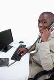 Seitenansicht eines männlichen Sekretärs, der das Telefon bei der Anwendung von a beantwortet Stockbild