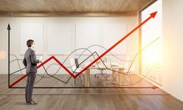 Seitenansicht eines Mannes, der Diagramme auf Konferenzsaalwand betrachtet Lizenzfreies Stockbild