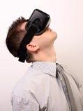 Seitenansicht eines Mannes, der einen Oculus-Risses 3D VR-virtueller Realität Kopfhörer, erforschend trägt und hoch aufwärts scha Lizenzfreies Stockbild
