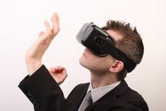 Seitenansicht eines Mannes, der einen Oculus-Risses 3D VR-virtueller Realität Kopfhörer, etwas mit seinen Händen berührend trägt  Lizenzfreies Stockfoto
