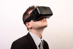 Seitenansicht eines Mannes, der einen Oculus-Risses 3D VR-virtueller Realität Kopfhörer, schauend aufwärts in einem schwarzen off Stockbild