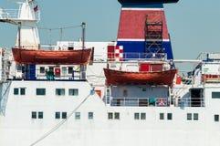 Seitenansicht eines Passagierschiffs und der orange Rettungsboote Stockfotografie