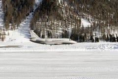 Seitenansicht eines Privatjets, der in den schneebedeckten Alpen in St. Moritz Switzerland sich entfernt stockfoto