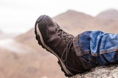 Seitenansicht eines schmutzigen wandernden Schuhes mit Bergen im backgroun stockfoto