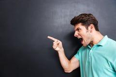 Seitenansicht eines verärgerten Mannes, der über schwarzem Hintergrund schreit Lizenzfreies Stockfoto