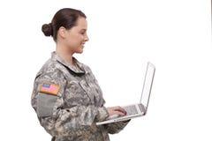 Seitenansicht eines weiblichen Soldaten, der Laptop verwendet Stockfotos