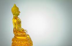 Seitenansicht gelber Glas-Buddha-Statue auf weißem BAC Lizenzfreie Stockfotografie