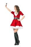 Seitenansicht herrlicher Santa Claus-Frau, die selfie mit Handy nimmt Stockfotos