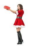 Seitenansicht junger hübscher Santa Claus-Frau, die Weihnachtsgeschenke gibt Stockbild
