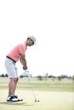 Seitenansicht Mannes des von mittlerem Alter Golf am Kurs spielend stockbild