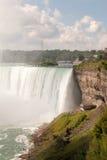 Seitenansicht Niagara Falls mit Leuten in den gelben Klagen Stockbild