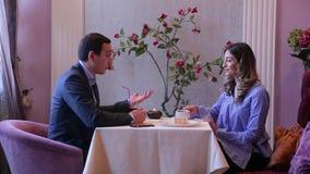 Seitenansicht, reizend Paare, Mann in der Klage und hübsches brunette Mädchen sitzen bei Tisch mit Kerze und Kaffee zu trinken un stock video footage