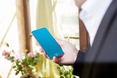 Seitenansicht schoss von den Händen eines Mannes unter Verwendung des intelligenten Telefons in Innenraum, r stockfoto