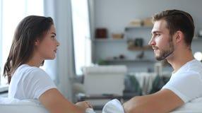 Seitenansicht Unterhaltungsauf einer Couch zu Hause von sitzen der Paare und von sich schauen lizenzfreies stockfoto