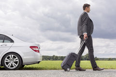 Seitenansicht in voller Länge des jungen Geschäftsmannes mit dem Gepäck, das aufgegliedertes Auto an der Landschaft lässt Lizenzfreie Stockbilder