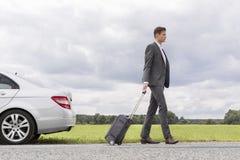 Seitenansicht in voller Länge des jungen Geschäftsmannes mit dem Koffer, der aufgegliedertes Auto an der Landschaft lässt Stockfotos
