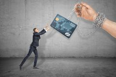 Seitenansicht in voller Länge Kleinunternehmers, der heraus erreicht, um die Kreditkarte zu ergreifen gehalten auf Kette durch ri lizenzfreie stockfotografie