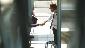 Seitenansicht in voller Länge von den Geschäftsmännern, die Hände im Bürogebäude rütteln Lizenzfreie Stockfotos