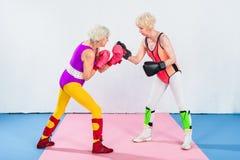 Seitenansicht von den älteren Sportlerinnen in den Boxhandschuhen kämpfend und schauend lizenzfreies stockbild