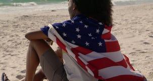 Seitenansicht von den Afroamerikanerpaaren eingewickelt in der amerikanischen Flagge, die zusammen auf dem Strand 4k sitzt stock video footage