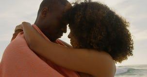 Seitenansicht von den Afroamerikanerpaaren eingewickelt in der Decke auf dem Strand 4k stock footage